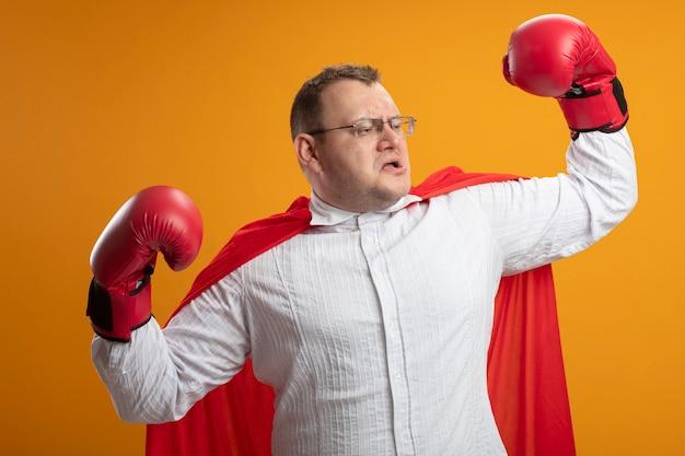 Pewny siebie dorosły słowiański superbohater w czerwonej pelerynie w okularach i rękawiczkach pudełkowych robi silny gest patrząc w bok odizolowany na pomarańczowej ścianie