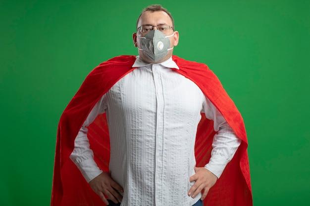 Pewny siebie dorosły superbohater w czerwonej pelerynie w okularach i masce ochronnej patrząc z przodu, trzymając ręce na talii odizolowane na zielonej ścianie