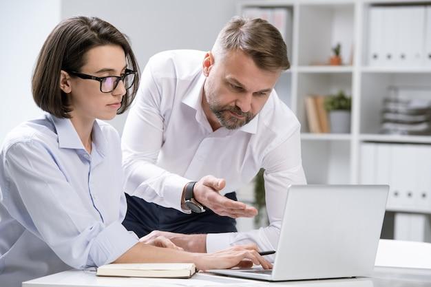 Pewny siebie ekonomista wskazujący na wyświetlacz laptopa i pokazujący informacje online koledze na spotkaniu