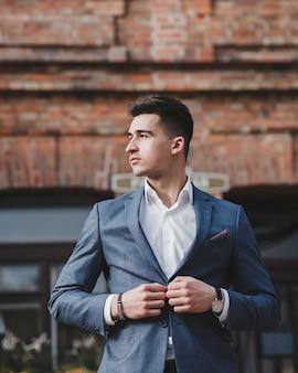 Pewny siebie elegancki przystojny młody człowiek stojący w mieście na sobie ładny garnitur