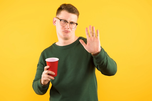 Pewny siebie facet w zielonym swetrze gospodarstwa czerwony plastikowy kubek pokazano przystanek gest na żółto