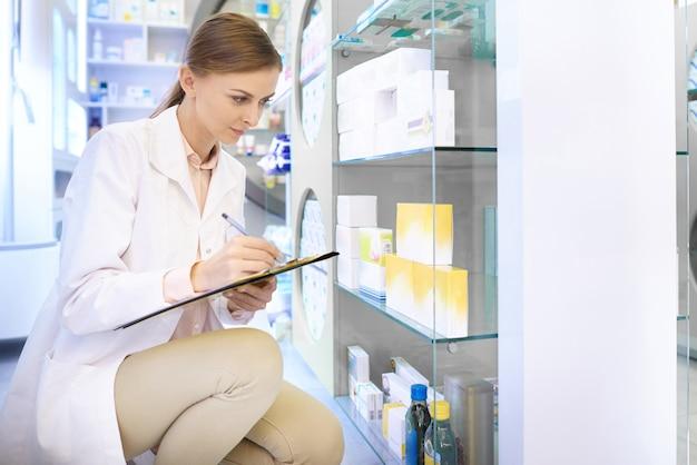 Pewny siebie farmaceuta robi inwentaryzację w aptece