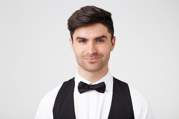 Pewny siebie flirtujący przystojny, elegancko ubrany ciemnowłosy facet z czarną muszką