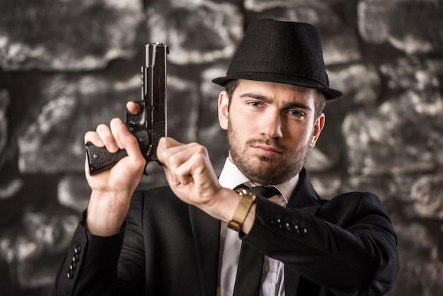 Pewny siebie gangster człowiek w garniturze i kapeluszu siedzi przy stole.