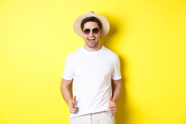 Pewny siebie i bezczelny facet na wakacjach flirtuje z tobą, wskazując palcem na aparat i mrugając, ubrany w letni kapelusz z okularami przeciwsłonecznymi, żółte tło.