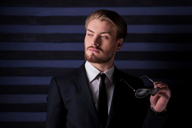 Pewny siebie i dobrze wyglądający. portret przystojnego młodego mężczyzny w formalwear, trzymającego okulary przeciwsłoneczne i odwracającego wzrok, stojąc na tle pasiastych