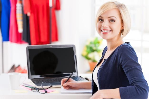 Pewny siebie i kreatywny. piękna młoda kobieta patrząca przez ramię i uśmiechnięta siedząc w swoim miejscu pracy