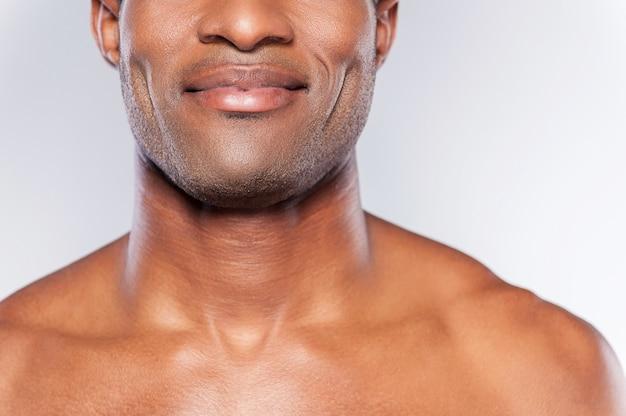 Pewny siebie i zadowolony. przycięty obraz młodego afrykańskiego mężczyzny bez koszuli uśmiechającego się stojąc na szarym tle