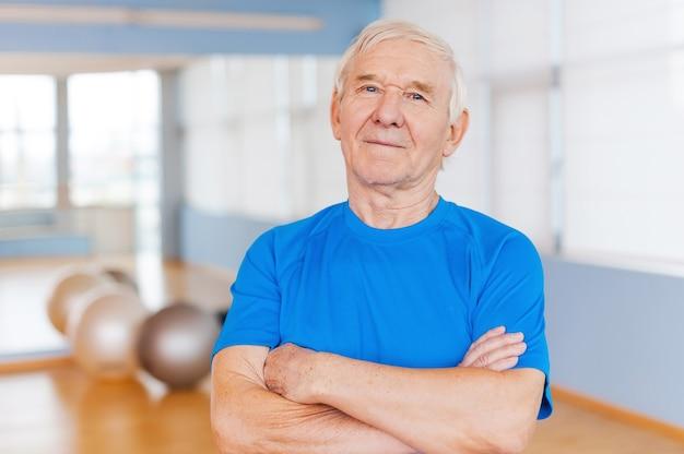 Pewny siebie i zdrowy. pewny siebie starszy mężczyzna trzymający skrzyżowane ręce i patrzący na kamerę stojąc w klubie fitness ze sprzętem sportowym leżącym w tle