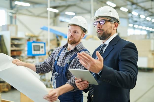 Pewny siebie inwestor biznesowy odwiedzający fabrykę i rozmawiający z inżynierem