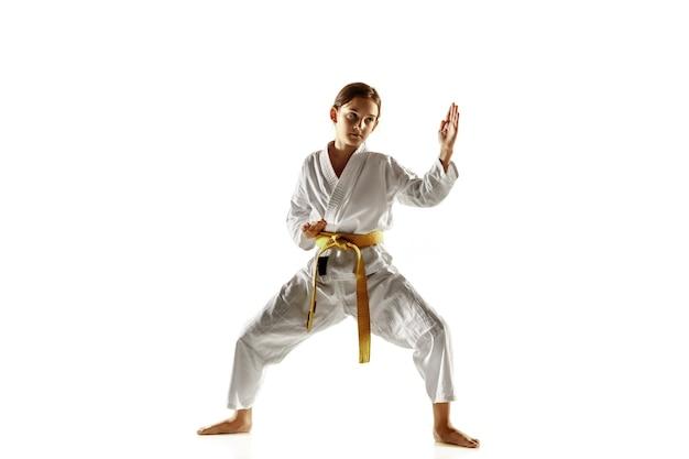 Pewny siebie junior w kimonie ćwiczący walkę wręcz, sztuki walki. młody żeński wojownik z żółtym pasem s trening na białej ścianie. pojęcie zdrowego stylu życia, sportu, akcji.