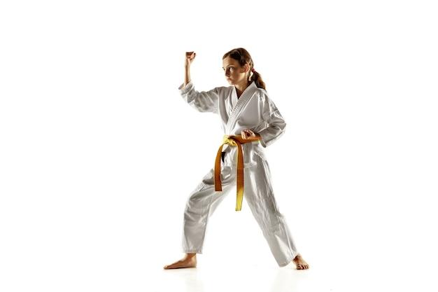 Pewny siebie junior w kimono uprawiający walkę wręcz, sztuki walki. młody żeński wojownik z żółtym pasem s trening na białej ścianie. pojęcie zdrowego stylu życia, sportu, akcji.