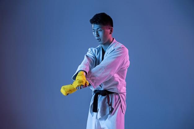 Pewny siebie koreańczyk w kimonie ćwiczy walkę wręcz, sztuki walki.