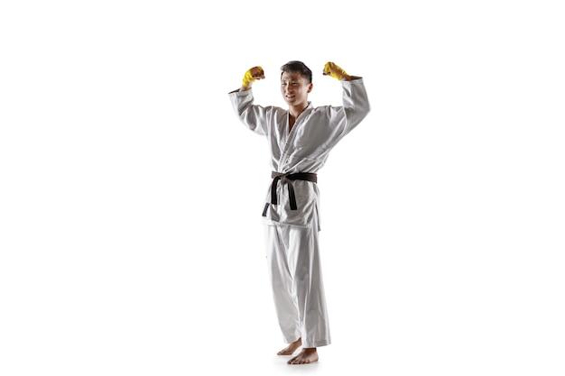 Pewny siebie koreański mężczyzna w kimonie ćwiczący walkę wręcz, sztuki walki. młody mężczyzna wojownik z czarnym pasem świętuje wygraną na białym tle na białej ścianie. pojęcie zdrowego stylu życia, sportu.