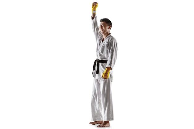 Pewny siebie koreański mężczyzna w kimonie ćwiczący walkę wręcz, sztuki walki. młody mężczyzna wojownik z czarnym pasem świętuje wygraną na białym tle na tle białego studia. pojęcie zdrowego stylu życia, sportu.