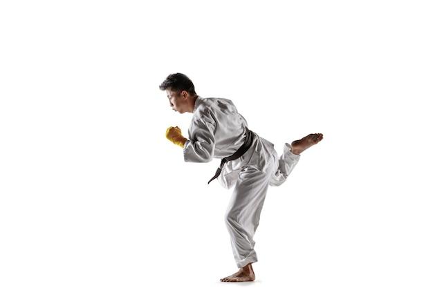 Pewny siebie koreański mężczyzna w kimonie ćwiczący walkę wręcz, sztuki walki. młody mężczyzna wojownik z czarnym pasem szkolenia na białym tle studio. pojęcie zdrowego stylu życia, sportu.