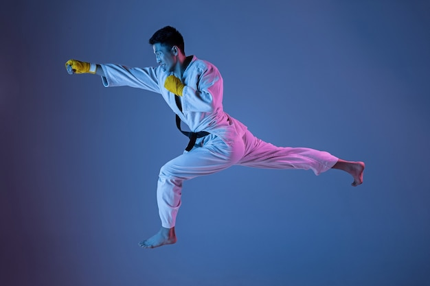 Pewny Siebie Koreański Mężczyzna W Kimonie ćwiczący Walkę Wręcz, Sztuki Walki. Młody Mężczyzna Wojownik Z Czarnym Pasem Treningowym Na Gradientowym Tle W świetle Neonowym. Pojęcie Zdrowego Stylu życia, Sportu. Darmowe Zdjęcia