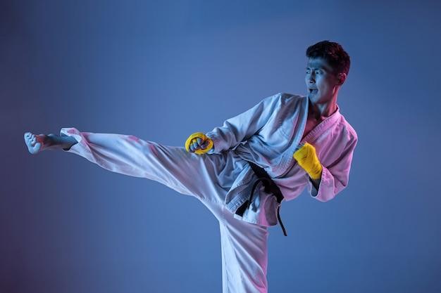 Pewny siebie koreański mężczyzna w kimonie ćwiczący walkę wręcz, sztuki walki. młody mężczyzna wojownik z czarnym pasem treningowym na gradientowym tle w świetle neonowym. pojęcie zdrowego stylu życia, sportu.