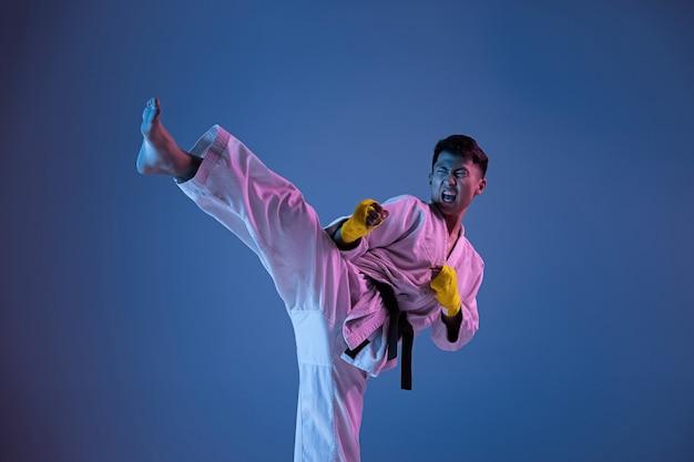Pewny siebie koreański mężczyzna w kimonie ćwiczący walkę wręcz, sztuki walki. młody mężczyzna wojownik z czarnym pasem treningowym na ścianie gradientowej w świetle neonowym. pojęcie zdrowego stylu życia, sportu.
