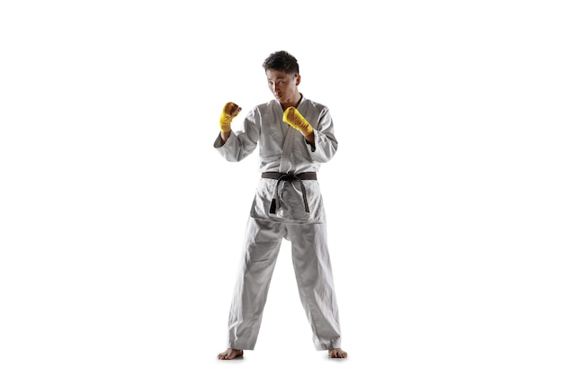Pewny siebie koreański mężczyzna w kimonie ćwiczący walkę wręcz, sztuki walki. młody mężczyzna wojownik z czarnym pasem treningowym odizolowywającym na białej ścianie. pojęcie zdrowego stylu życia, sportu.