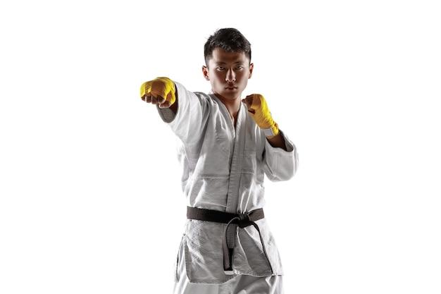 Pewny siebie koreański mężczyzna w kimonie ćwiczący walkę wręcz, sztuki walki