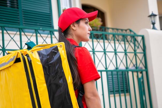 Pewny siebie kurier łaciński dostarcza zamówienie i odwraca wzrok. profesjonalna młoda piękna kobieta dostarczająca żółty plecak i ubrana w czerwony mundur. dostawa żywności i koncepcja poczty
