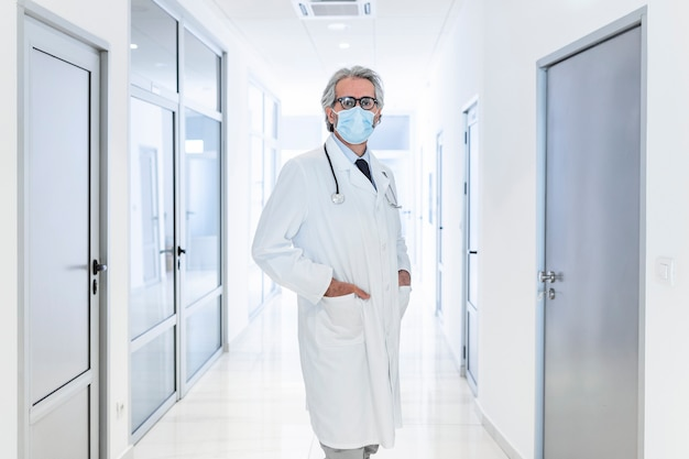 Pewny siebie lekarz noszący ochronną maskę na twarz, stojąc na korytarzu w szpitalu