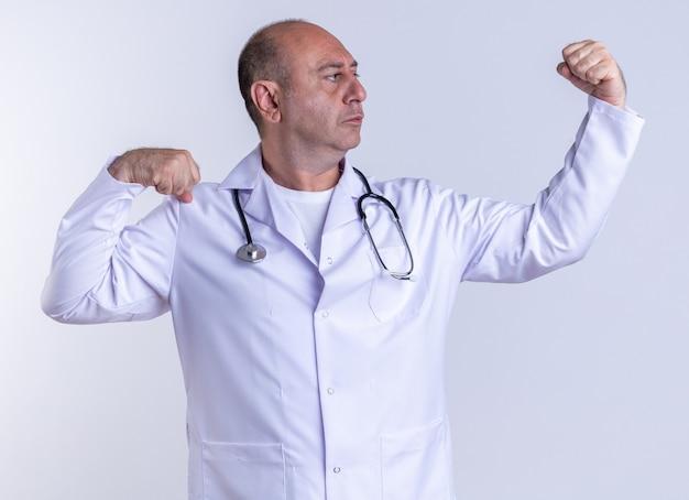 Pewny siebie lekarz w średnim wieku, ubrany w szatę medyczną i stetoskop, wykonujący silny gest, patrząc na swoją pięść odizolowaną na białej ścianie