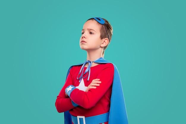 Pewny siebie mały chłopiec w kostiumie superbohatera krzyżujący ramiona i odwracający wzrok, stojąc przed turkusem