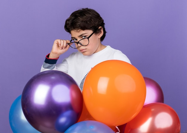 Pewny siebie mały chłopiec w okularach stojący za balonami