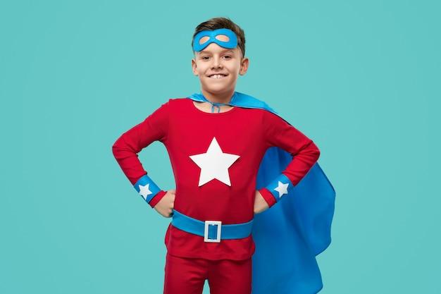 Pewny siebie mały super bohater z uśmiechem