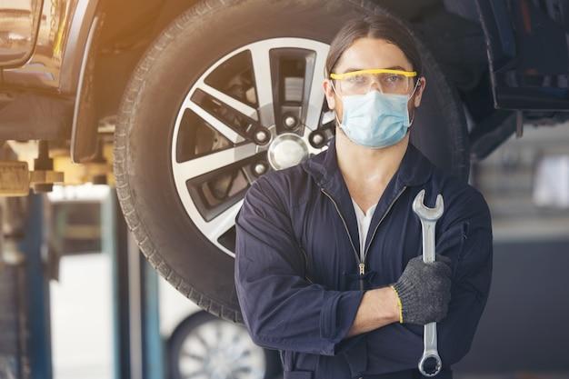 Pewny siebie mechanik stojący w warsztacie