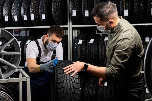 Pewny siebie mechanik w masce i klient sprawdzający opony w sklepie, prowadzący rozmowę w sklepie, klient zamierza dokonać zakupu