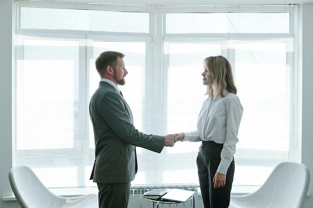 Pewny siebie menadżer hr ściska dłoń młodej odnoszącej sukcesy kandydatki, gratulując jej rozpoczęcia nowej kariery po rozmowie kwalifikacyjnej