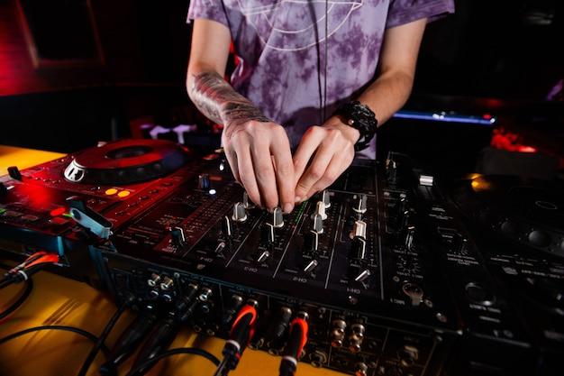 Pewny siebie męski disc jockey przy gramofonie. podczas imprezy dj gra na najlepszych, znanych odtwarzaczach cd w nocnym klubie. edm, koncepcja partii. życie w klubie nocnym. bliska strzał.