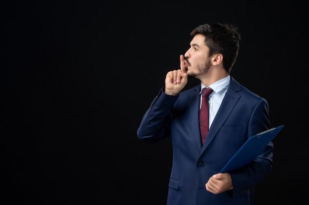 Pewny siebie męski pracownik biurowy w garniturze trzymający dokumenty i wykonujący gest ciszy na izolowanej ciemnej ścianie