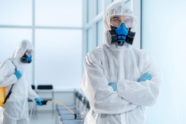 Pewny siebie męski środek odkażający stojący w holu szpitala. pojęcie ochrony zdrowia.