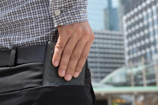 Pewny siebie mężczyzna pozuje do bezpiecznego przechowywania portfela