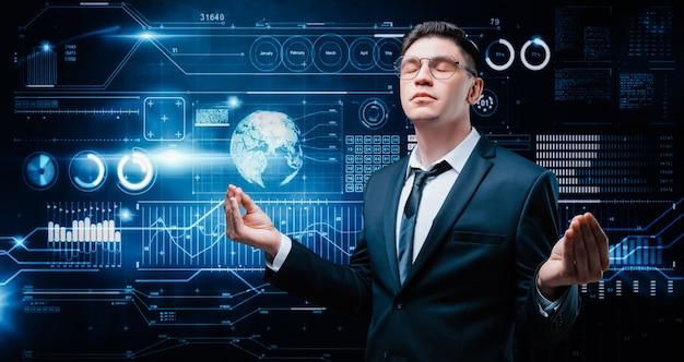 Pewny siebie mężczyzna stoi w garniturze na tle hologramu giełdowego. on medytuje. makler giełdowy i handlowiec. inwestycja biznesowa.