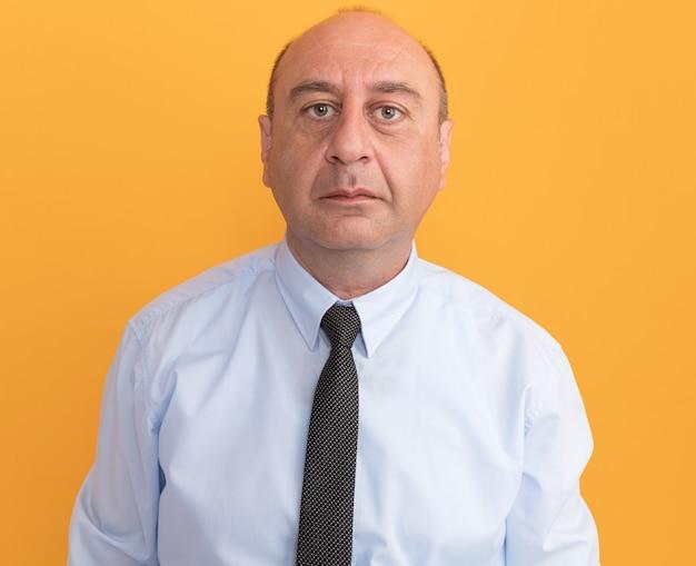 Pewny siebie mężczyzna w średnim wieku na sobie białą koszulkę z krawatem na białym tle na pomarańczowej ścianie