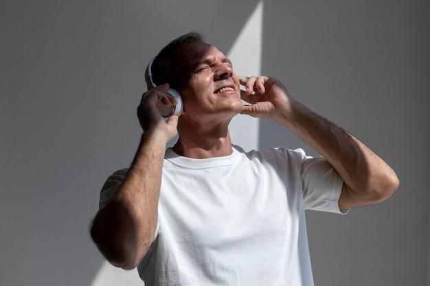 Pewny siebie mężczyzna w średnim wieku słuchający muzyki