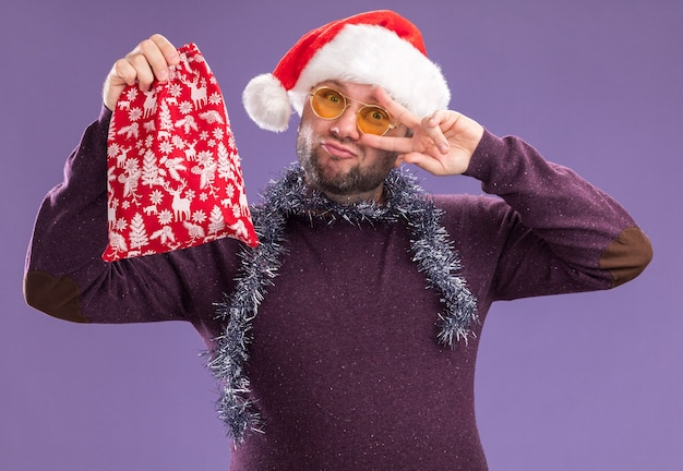 Pewny siebie mężczyzna w średnim wieku, ubrany w santa hat i girlandę z blichtru wokół szyi z okularami trzymającymi worek prezentów świątecznych, patrząc na kamerę pokazującą symbol v-znak w pobliżu oka na białym tle na fioletowym tle