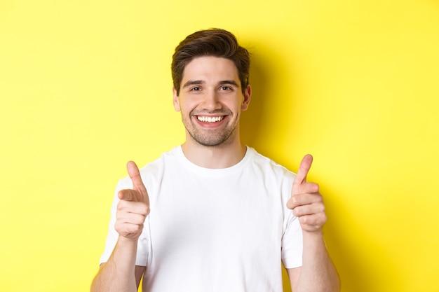 Pewny siebie mężczyzna, wskazując palcami na aparat i uśmiechając się, chwaląc cię, stojąc na żółtym tle.