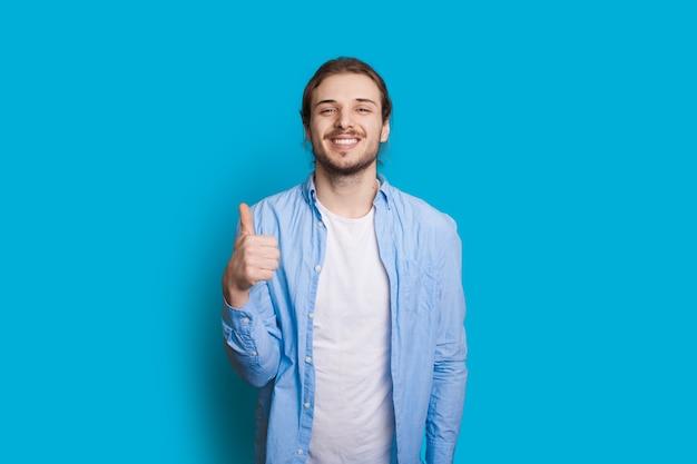 Pewny siebie mężczyzna z brodą i długimi włosami pokazuje podobny znak na niebieskiej ścianie