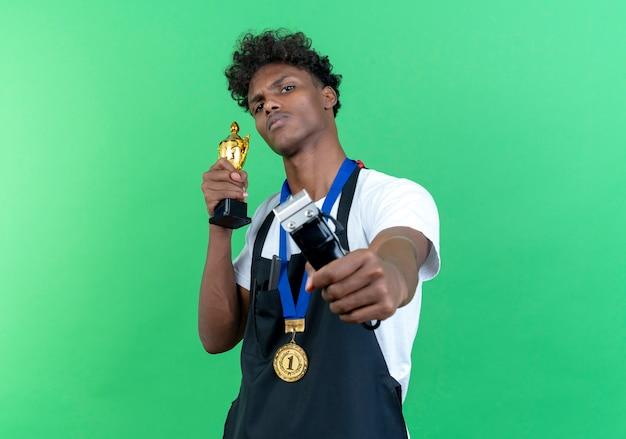 Pewny siebie młody afro-amerykański męski fryzjer w mundurze i medalu, trzymając maszynkę do strzyżenia włosów do aparatu z puchar zwycięzcy na białym tle na zielonym tle