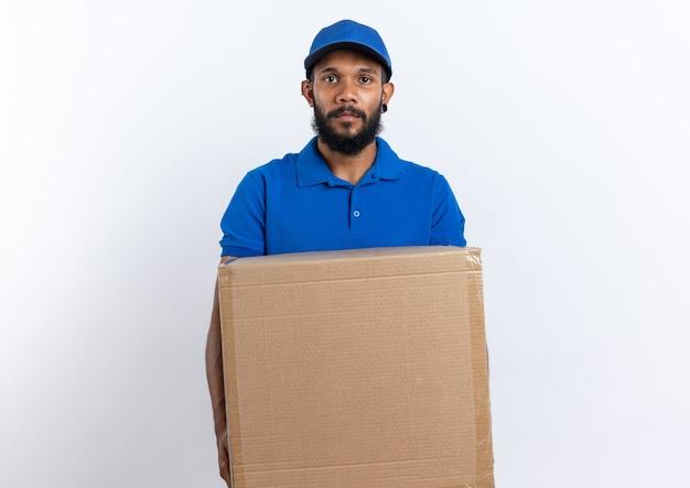 Pewny siebie młody afro-amerykański mężczyzna dostawy trzymający duży karton na białym tle na białej ścianie z miejscem na kopię