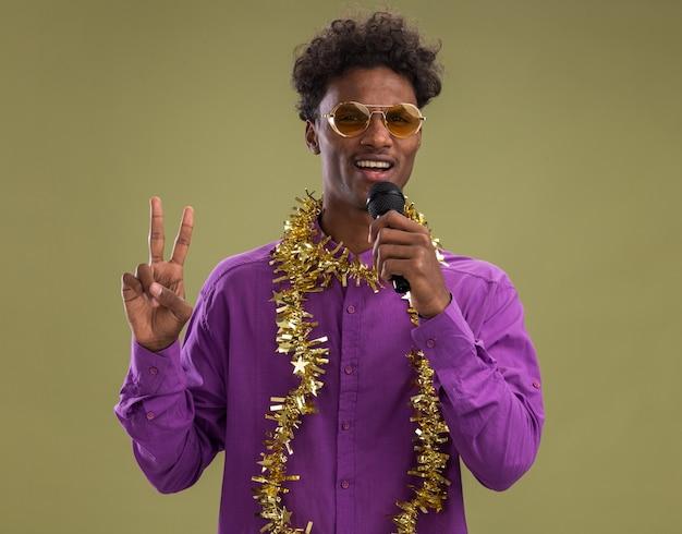 Pewny siebie młody afro-amerykański mężczyzna w okularach z świecącą girlandą na szyi mówi do mikrofonu patrząc na kamerę robi znak pokoju na tle oliwkowej zieleni
