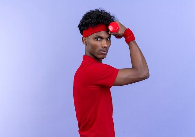 Pewny siebie młody afro-amerykański sportowy mężczyzna ubrany w opaskę i opaskę, trzymając hantle wokół głowy