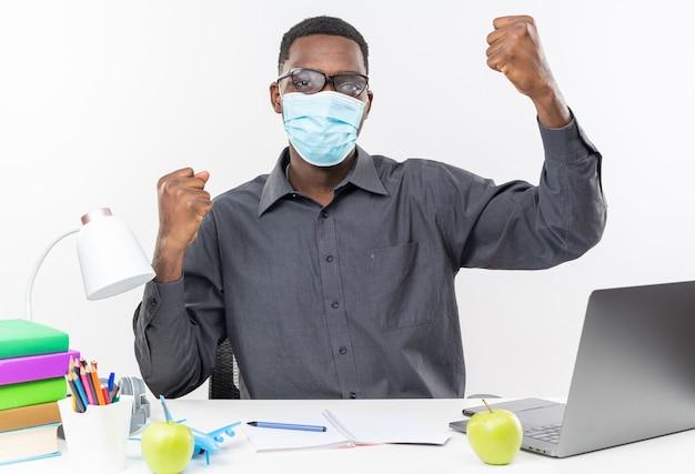 Pewny siebie młody afroamerykański student w okularach optycznych noszący maskę medyczną siedzący przy biurku z szkolnymi narzędziami podnoszącymi pięści w górę