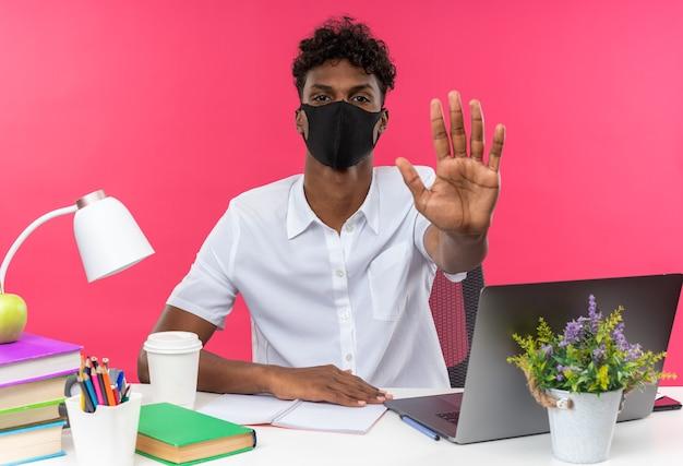 Pewny siebie młody afroamerykański uczeń noszący maskę siedzącą przy biurku z szkolnymi narzędziami gestykulującym znakiem stop na białym tle na różowej ścianie